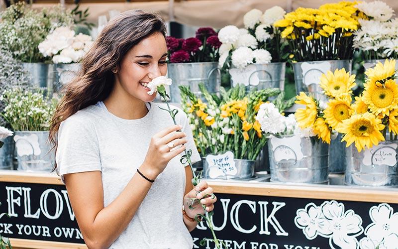 Mujer sonriendo con una flor