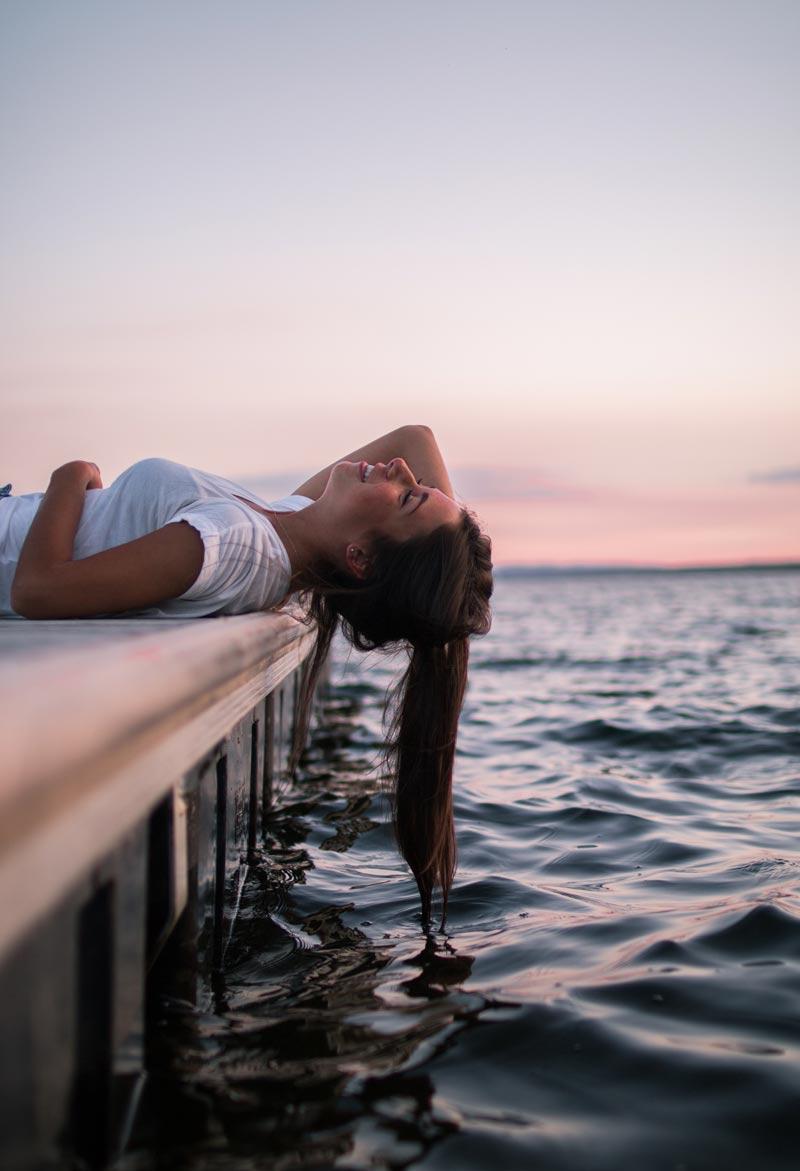 Mujer descansando a la orilla del mar