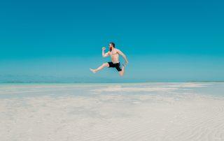 Hombre saltando en la playa