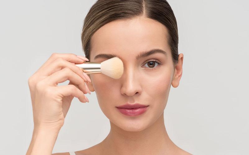Mujer aplicando una base de maquillaje en el rostro