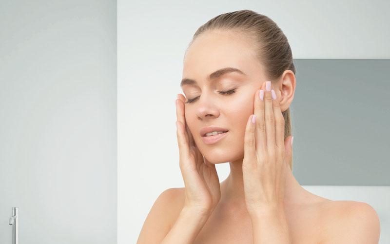 Mujer aplicando crema hidratante en la cara