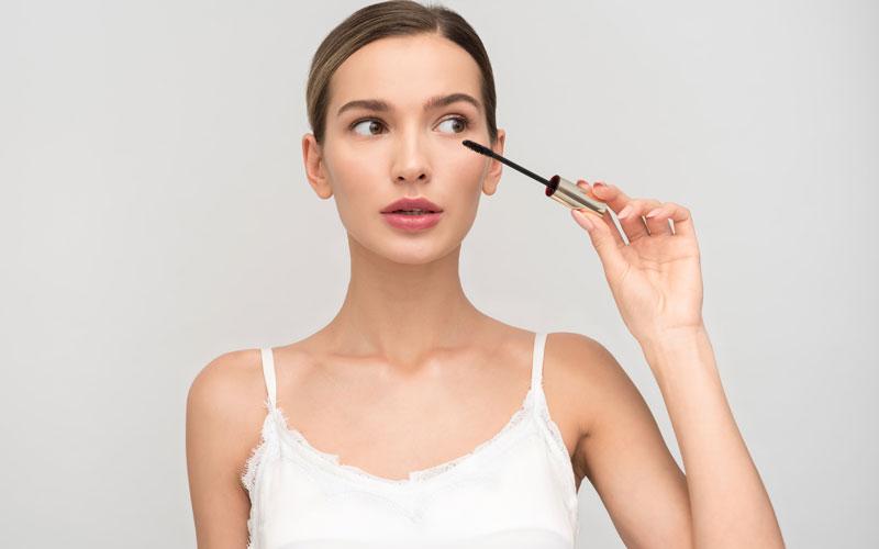 Mujer aplicando rimmel en los ojos